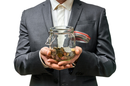 budgets: Man in black suit holding money jar with coins isolated on white background Stock Photo