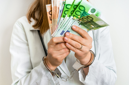 Doctor with euro money and handcuffs - corruption and bribe concept in medicine