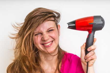 Beautiful young woman dries hair with red hair dryer