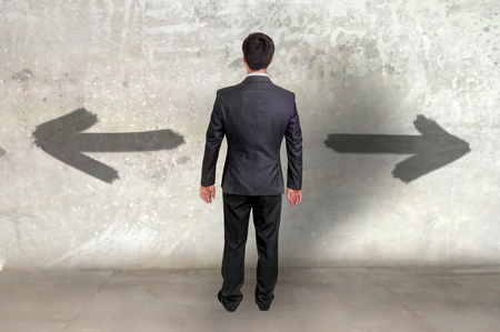 he is different: Businessman between two different choices, he looking at arrows on the wall