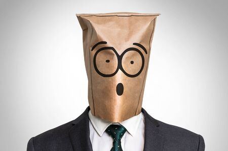 Businessman with a paper bag on the head - with surprised face