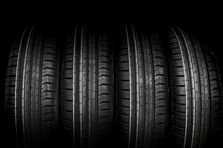 winter tires: Car tires in row isolated on black background