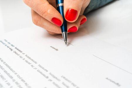 Mujer de negocios con bolígrafo firmando documento de contrato