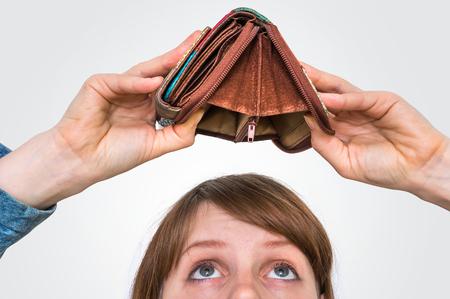 Business woman holding an empty wallet, she hasn't money Standard-Bild