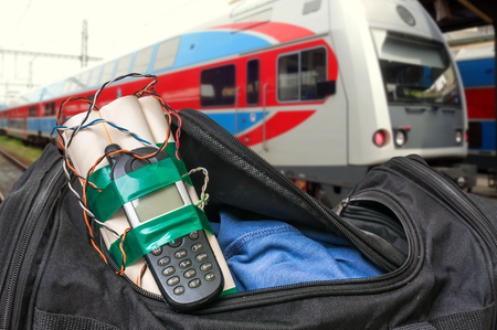 Dynamite bomb with phone in terrorist bag on train station - terrorism concept