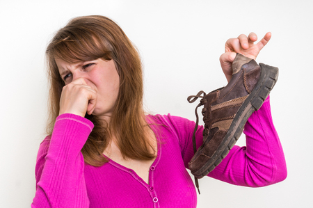 Woman holding dirty stinky shoes - unpleasant smell concept