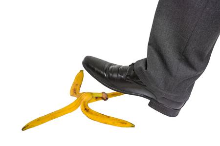 Businessman stepping on banana peel on white - business risk concept