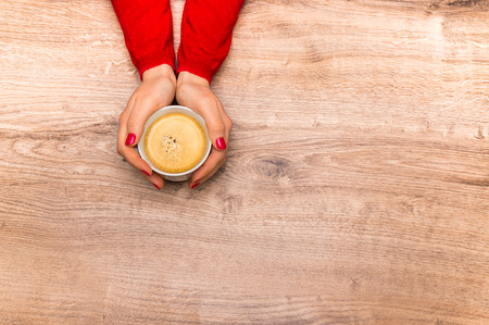 Female hands holding a cup of hot coffee on wooden table 스톡 콘텐츠