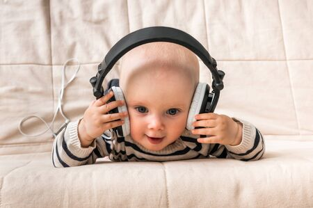 Happy smiling baby with headphones listens to music at home