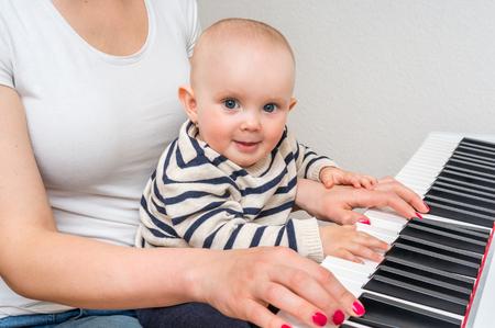 家でピアノを演奏する彼女のかわいい赤ちゃんを教える母します。 写真素材 - 77439953