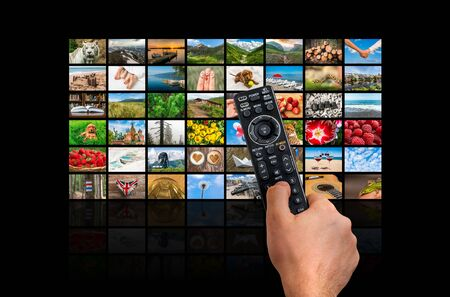Screens forming a big multimedia broadcast video wall with remote control - broadcasting and multimedia concept Stock Photo