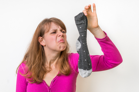 Woman holding dirty stinky socks - unpleasant smell concept