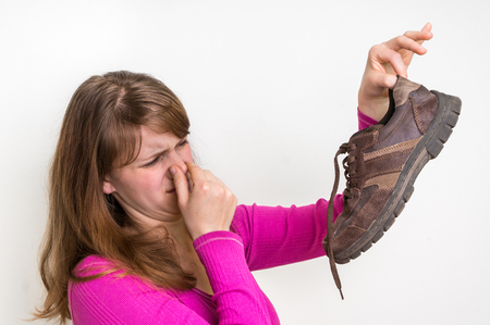 Woman with stinky shoe of her husband - unpleasant smell concept Stock Photo