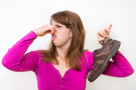Woman with stinky shoe of her husband - unpleasant smell concept 스톡 콘텐츠
