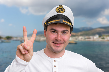 Happy captain with sailor cap showing victory sign - marine concept Stock Photo