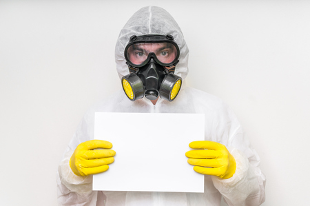 Man in coveralls with gas mask is holding blank white paper - ecology and pollution concept