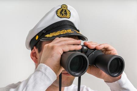 Captain looks through a binoculars - marine concept