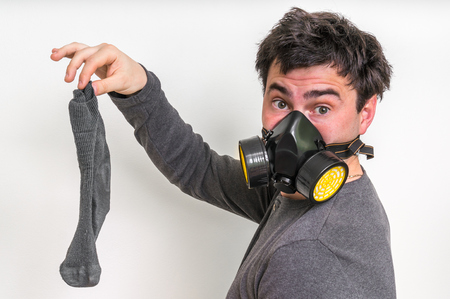 Man with gas mask is holding stinky sock - unpleasant smell concept Stockfoto