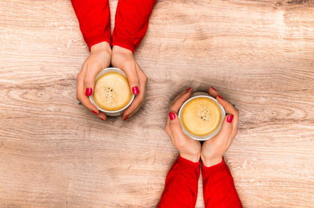 Female hands holding a cup of hot coffee on wooden table Stock Photo