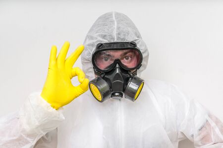 Man in coveralls with gas mask is showing O.K. symbol - ecology and pollution concept Stock Photo