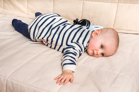Cute baby is lying and resting on sofa with headphones at home Stock Photo