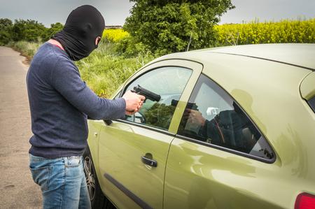 Mannelijke dief of terrorist wijst een pistool op de bestuurder, hij probeert een auto te stelen