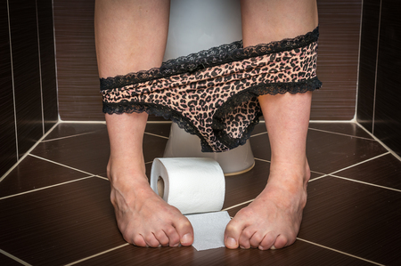 constipated: Woman suffers from diarrhea is sitting on toilet bowl and toilet paper roll near her legs Stock Photo