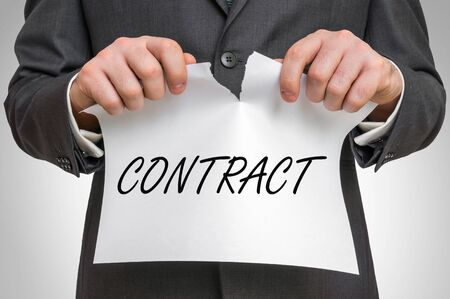 Businessman tearing paper with contract word - business idea concept