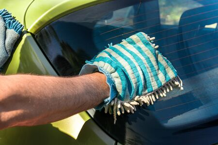 valet: Man washing his green car - car washing and car cleaning concept