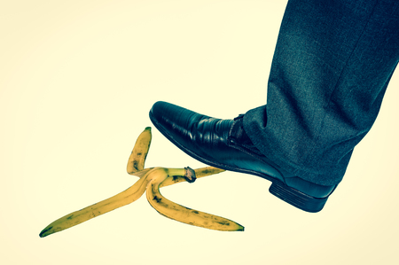 Businessman stepping on banana peel - business risk concept - retro style Stock Photo