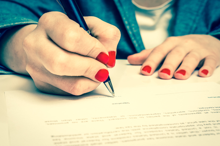 autograph: Business woman with ballpoint pen signing contract document - retro style