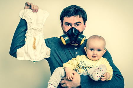 Father with gas mask is holding dirty diaper and little baby girl - baby care concept - retro style