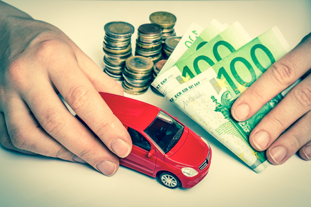 Toy car and euro money banknotes - insurance, rent and buying car concept - retro style