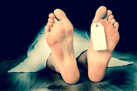 Dead woman lying on the floor under white cloth with blank tag on feet - retro style