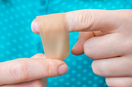 Young woman puts a plaster on her injured finger Archivio Fotografico