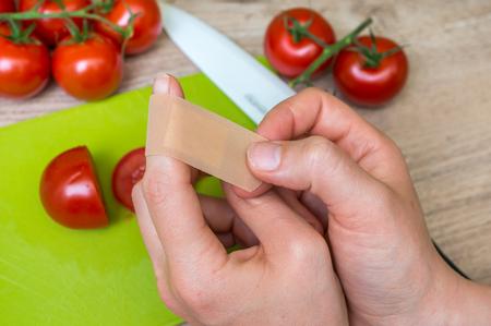 若い女性は彼女の指 - キッチンで傷害に石膏を適用します。