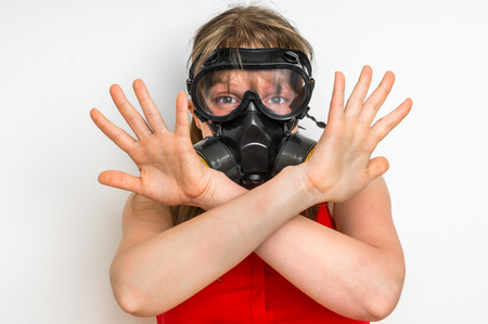 Young business woman with gas mask is showing negative gesture