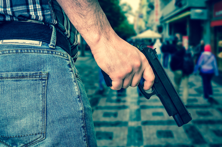 Killer with pistol and crowd of people on the street - murder and crime concept - retro style Stock Photo
