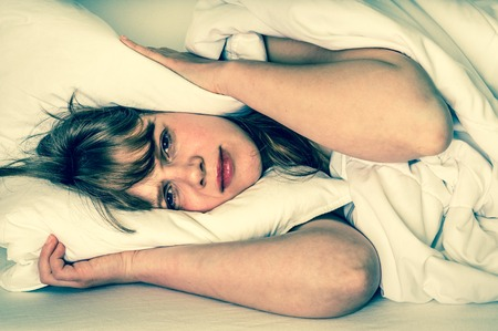 headaches: Young woman trying to sleep, she covering ears with pillow - retro style