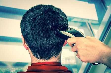 Hairdresser cutting black hair with electric hair clipper in barber shop - retro style Stock Photo