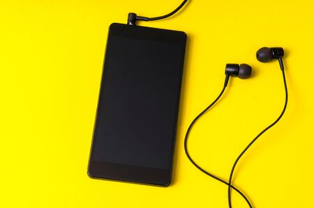 Mobile phone with headphones isolated on yellow background - close-up view Stock Photo