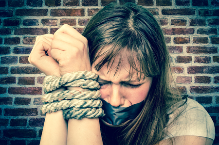 Tied rope hands of abused woman isolated on bricks background - violence concept - retro style