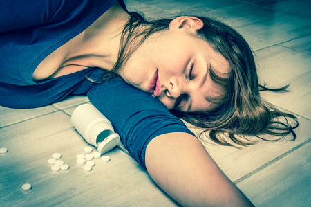 Depression woman lying on the floor at home after an overdose of pills - woman committing suicide with pills - retro style