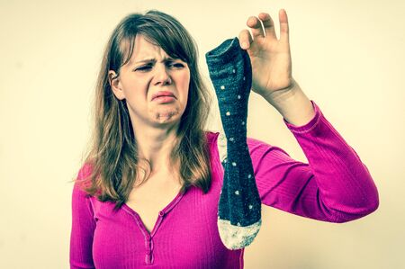 Woman holding dirty stinky socks - unpleasant smell concept - retro style