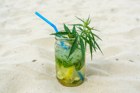 Mojito drink with leafs of marijuana plant on sand