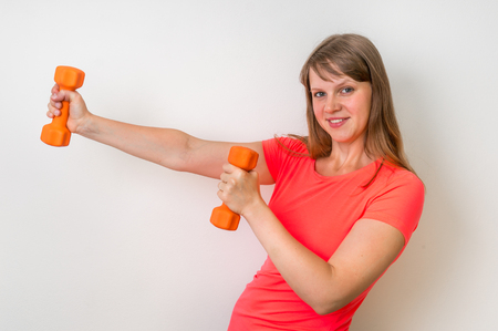 Fitness woman doing exercises with dumbbells in the gym Stock Photo