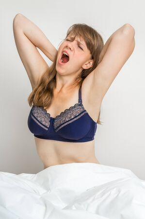 bedroom: Attractive young woman is yawning in bed after sleeping