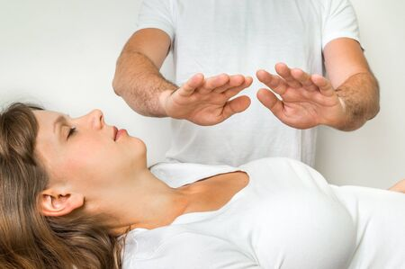 energy healing: Young woman getting reiki healing therapy - alternative medicine concept Stock Photo