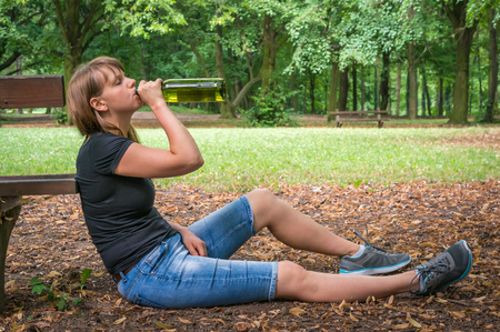 Lonely drunken woman holding a wine bottle in the park - alcoholism concept Stock Photo
