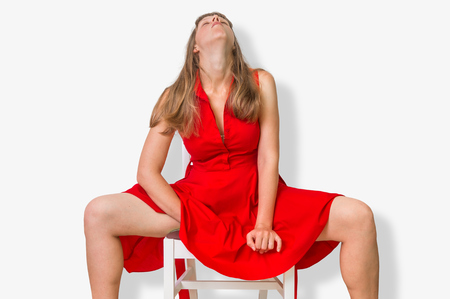 Attractive woman is sitting on chair, masturbating and covering herself with red dress